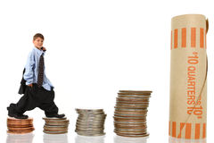 Young Boy in Suit Climbing Stacks of Money Royalty Free Stock Images