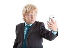 Young boy in suit making selfie with big smartphone, isolated white background Royalty Free Stock Photo