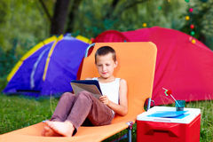 Young boy in summer camp, relaxing with tablet Stock Image