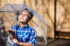 Young boy in a sun shower  with umbrella Stock Image