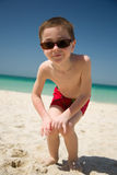 Young boy in sunglasses look at the camera at the sandy beach Royalty Free Stock Images
