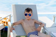 Young boy in a swimsuit on a shelf by the pool. A young boy in sunglasses in a swimsuit on a shelf by the pool in summer royalty free stock images