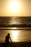 Young boy at sunset watching sailboat in distance Stock Photos