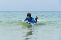 Young boy surfing in the sea Stock Photo
