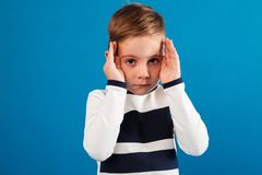 Young boy in sweater holding his hands near the eyes. And looking at the camera over blue background stock images