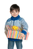 Young boy in a sweater holds a gift box Stock Image