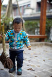 Young boy sweeping leaves Royalty Free Stock Photo