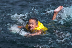Young boy swimming. Happy smiling young boy swimming in the water Royalty Free Stock Photography