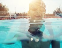 Young boy swimming with half of face under water backlit Stock Images