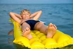 Young boy swimming on mattress in the sea Royalty Free Stock Photography