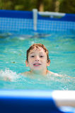 Young boy swimming in an outdoor pool. On a hot summer day Stock Photography