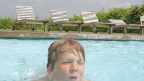 Young Boy Swimming In Outdoor Pool stock footage