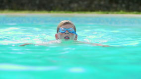 Young Boy Swimming In Outdoor Pool Stock Image