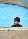 A young boy in  a swimming pool. A young boy in an all-in-one swimsuit in a swimming pool in the tropics Stock Images