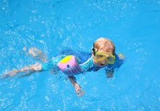 Young Boy in Swimming Pool. Young Boy in blue Swimming Pool with goggles arm bands and a uv protection suit Stock Photo