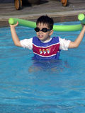 Young boy in the swimming-pool. Young boy wearing goggles and playing with swimming aid in a swimming-pool Royalty Free Stock Photo