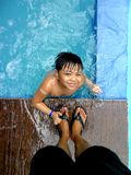 Young boy in a swimming pool and the feet of his parent Stock Photo