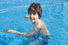 Young Boy is in the Swimming Pool. Young Boy is Have Fun in the Swimming Pool Royalty Free Stock Images