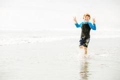 Young boy in swimming shorts and rushwest runs Royalty Free Stock Images
