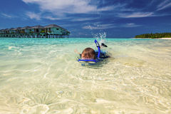 Young boy swimming and snorkeling in tropical lagoon Stock Photos