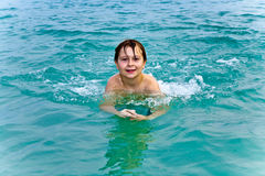 Young boy is swimming in the warm Royalty Free Stock Photos