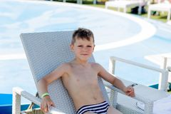 Young boy in a swimsuit on a shelf by the pool. In summer Stock Photo