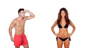 Young boy in swimwear looking at a girl in bikini Stock Image