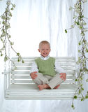 Young Boy on Swing. Young boy with green sweater vest on swing Royalty Free Stock Photos