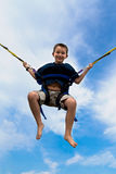 Young Boy Swinging High In The Air Stock Photo