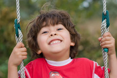 Young boy swinging and smiling Stock Photo