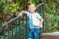 Young boy in t shirt going down stairs with a laptop in left hand stock photo