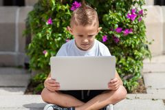 Young boy in t shirt inspecting laptop outdoor stock images