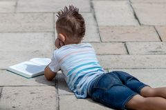 Young boy in t shirt reading book in a garden royalty free stock images