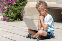 Young boy in t shirt inspecting laptop outdoor stock image