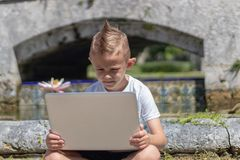Young boy in t shirt inspecting laptop outdoor royalty free stock photography