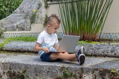 Young boy in t shirt inspecting laptop outdoor royalty free stock photos