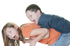 Young boy tackling girl Stock Photo