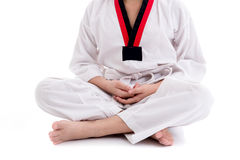 Young boy in taekwondo uniform doing meditation. Isolated on white Stock Images