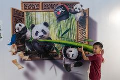 Trick art, painting, 3dlifelikeyoung boy takes part in the picture, indoors fun happy panda bbear. A young boy takes part in the photo, this is trick art, a Royalty Free Stock Photo