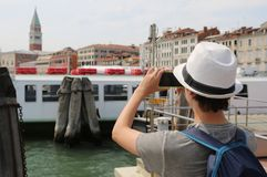 Young boy takes picutres with his smart phone in Venice stock image