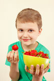 Young boy takes sweet red strawberry from the bowl Stock Photography