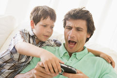 Young boy taking handheld game from man Stock Photos