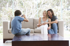 A young boy taking a photo of his parents sitting on a sofa Royalty Free Stock Image