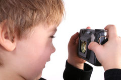 Young boy taking a photograph. Isolated photo of young boy taking a photograph with compact digital camera stock photography