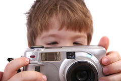 Young boy taking a photograph. Isolated photo of young boy taking a photograph with compact digital camera Royalty Free Stock Image