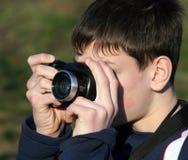 Young boy taking photos. With black camera Stock Photos