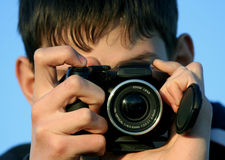 Young boy taking photos. With black camera Stock Photography