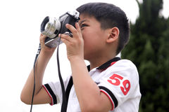 Young boy taking photos with vintage film camera Royalty Free Stock Photo
