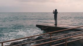 Young boy taking pictures of stormy sea. Man making photo standing at pier. Lonely boy taking video of windy ocean. Side view of y. Oung man taking photos at stock footage