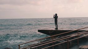Young boy taking video of rainy sea. Attractive man making photo at promenade. Lonely boy making pictures of stormy sea. Melanchol. Y young boy looking at ocean stock footage